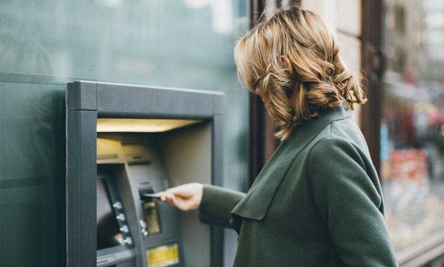 Mujer que usa un cajero automático para acceder a su dinero