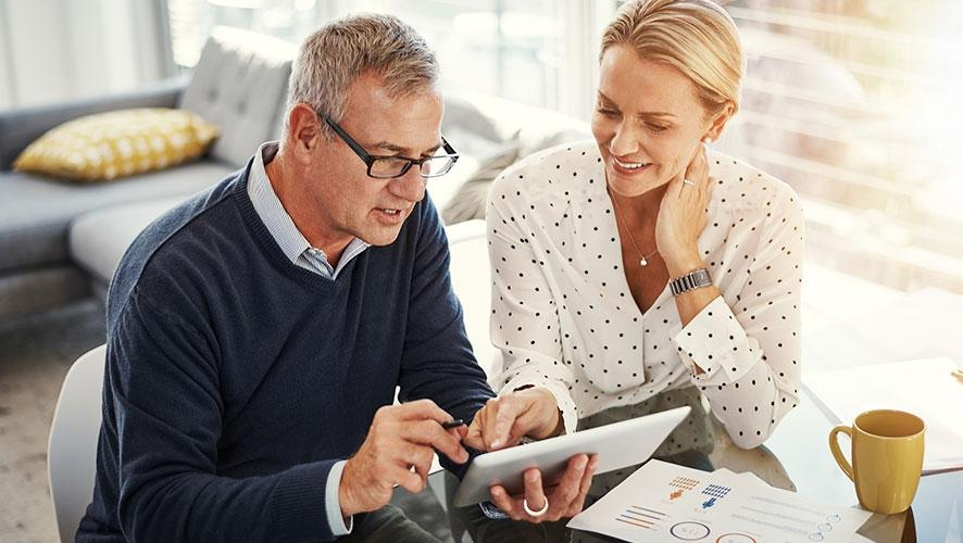 A man and woman work through paperwork to plan their retirement savings strategy.