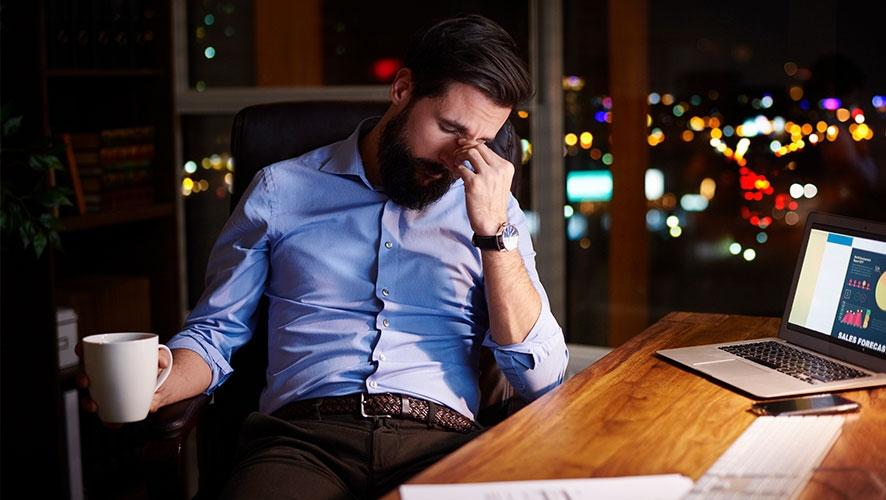 White-collar worker looking tired at his desk, representing working overtime