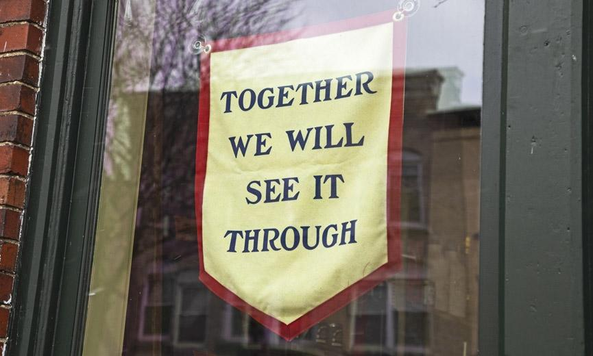 A sign in the window of a closed business due to COVID-19