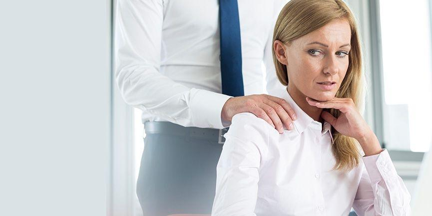 Woman at workplace looking uncomfortable as man touches her shoulder