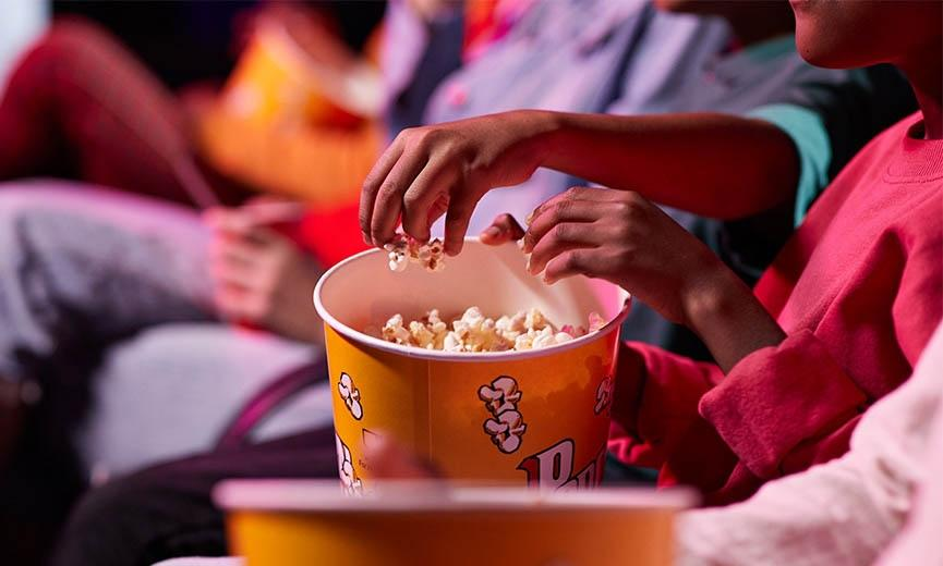 family eat popcorn while attending a movie in a theater