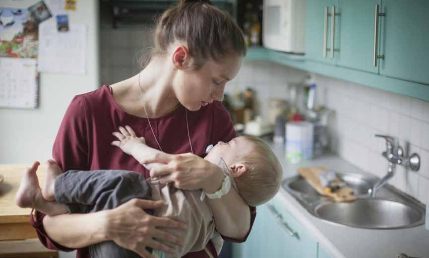 Woman cares for child at home, taking time under the Expanded California Family Rights Act.lifornia