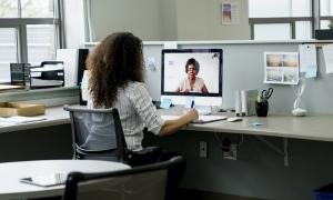An employee working at the office while talking to a coworker who is working from home.
