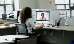 Un empleado que trabaja en la oficina mientras habla con un compañero que trabaja desde su casa.