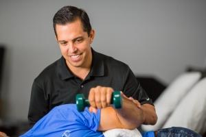 Andy del Rio helps a client with a hand exercise. Del Rio has been with Vargo Physical Therapy since it opened in 2000 and has benefited from the retirement and profit-sharing plan.
