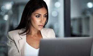 A business woman looks for data on computer for employees who might have taken premium tax credit.