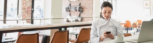 Chef que revisa su talón de pago con Paychex Flex