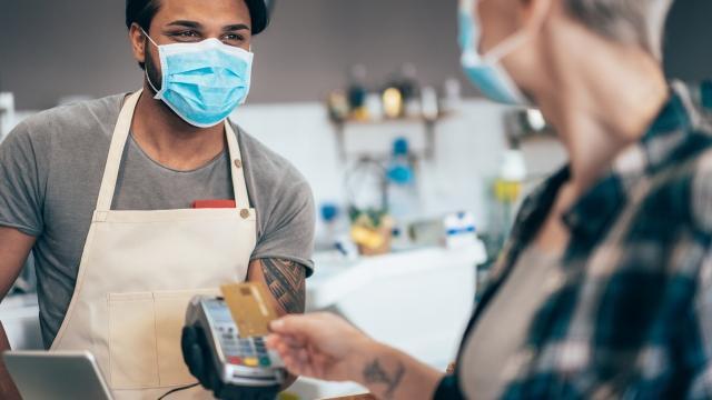 Un empleado y un cliente usan mascarillas para mantenerse a salvo.