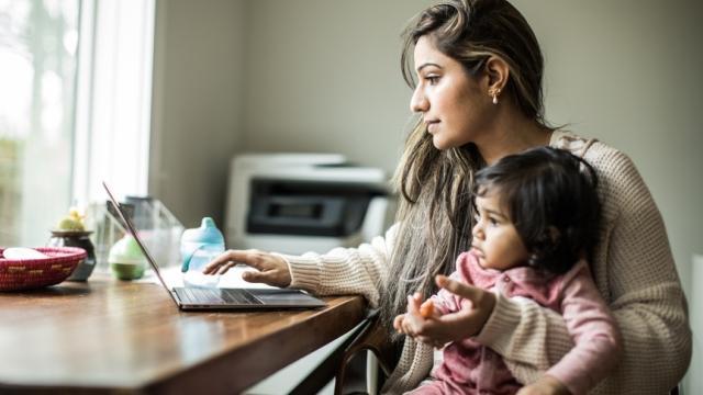 madre trabajando con un niño en el regazo