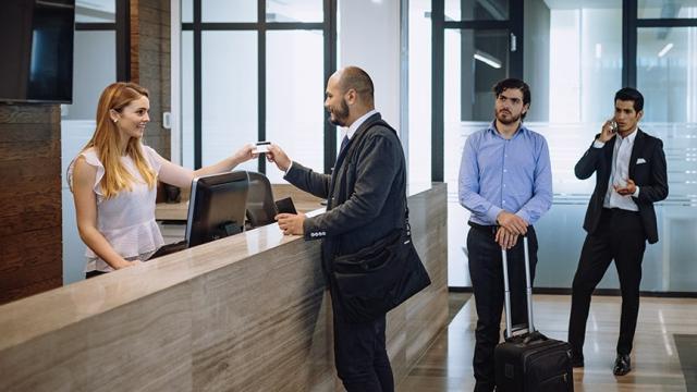 Una mujer registra a un empresario en un hotel. Los hoteles pueden solicitar una subvención para alojamiento en Ohio si cumplen con otros criterios.