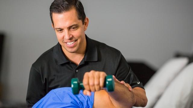 Andy del Rio ayuda a un cliente con un ejercicio para la mano. Del Rio ha sido parte de Vargo Physical Therapy desde su apertura en el año 2000 y se ha beneficiado del plan de jubilación y participación en las ganancias.