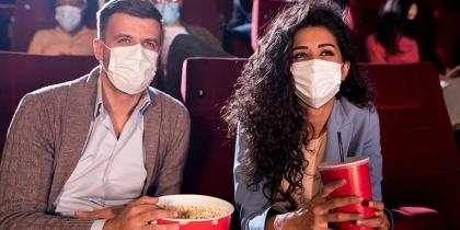 A man and a woman, both wearing masks, eat popcorn while attending a movie in a theater during the COVID-19 pandemic