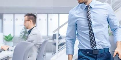un empleado se desplaza mientras otro trabaja frente a una computadora en una empresa de California
