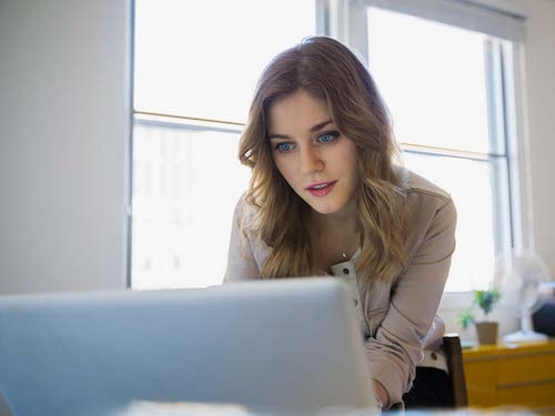 Young woman looking at laptop in small office